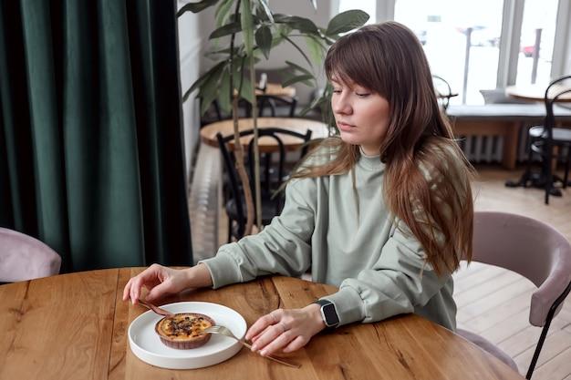 Vrij leuke vrouw zit in café eet cake