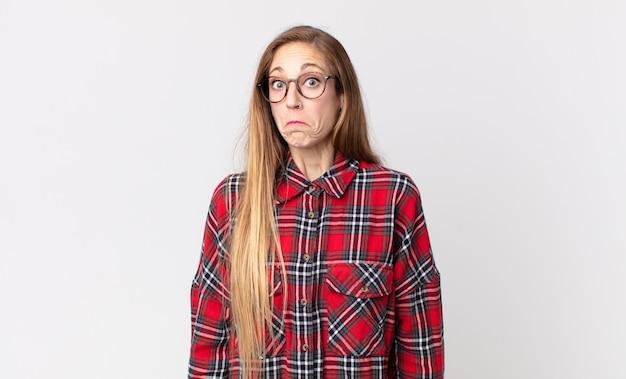 Vrij magere vrouw die zich verdrietig en gestrest voelt, van streek door een onaangename verrassing, met een negatieve, angstige blik