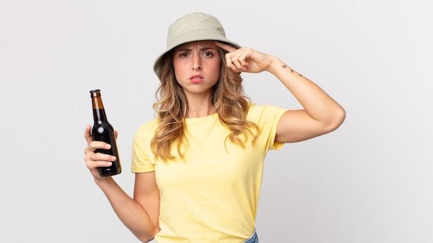 Vrij magere vrouw die zich verward en verbaasd voelt, laat zien dat je gek bent en een biertje vasthoudt. zomer concept