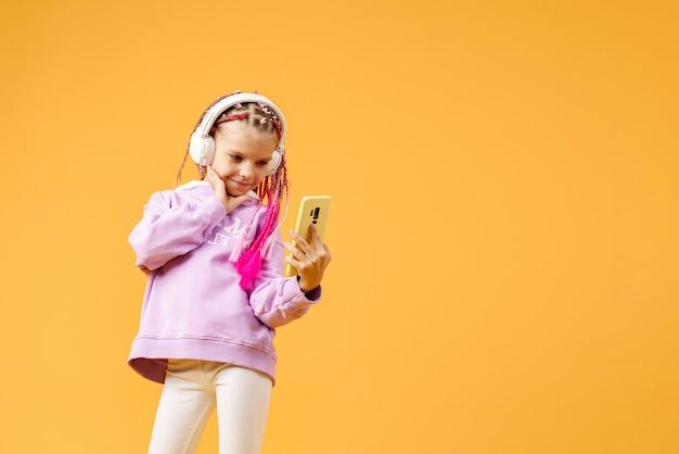 Vrij modern meisje met roze dreadlocks in hoofdtelefoons glimlachen