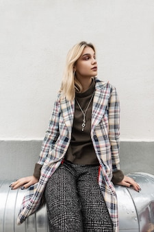 Vrij moderne jonge vrouw blonde in geruite stijlvolle blazer in modieuze broek zit op metalen pijp in de buurt van vintage gebouw op straat
