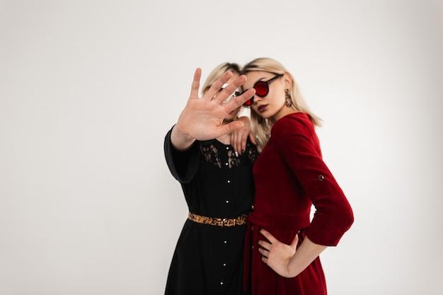 Vrij moderne modieuze tienermeisjes in mode kleding in stijlvolle gekleurde glazen knuffelen en dame in zwarte jurk