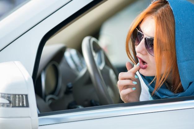 Vrij modieuze bedrijfsvrouwenbestuurder in sjaal en zonnebril die haar make-up controleren in een spiegel.