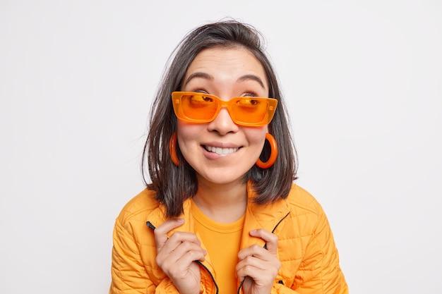 Vrij modieuze donkerharige aziatische vrouw bijt lippen kijkt weg draagt oranje zonnebril oorbellen jas gaat lopen tijdens zonnige lentedag geïsoleerd over witte muur. mensen stijl