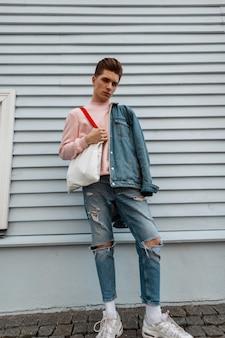 Vrij modieuze jonge man in roze sweatshirt in spijkerjasje in gescheurde spijkerbroek met stoffen tas poseren in de buurt van vintage gebouw in de stad op zomerdag. aantrekkelijke man in vrijetijdskleding met shopper buitenshuis.