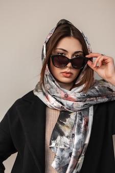 Vrij modieuze jonge vrouw model in stijlvolle elegante kleding opstijgt zonnebril en kijkt naar de camera. portret mooi meisje in seizoenskleding met zijden sjaal op hoofd in de buurt van muur in de stad.