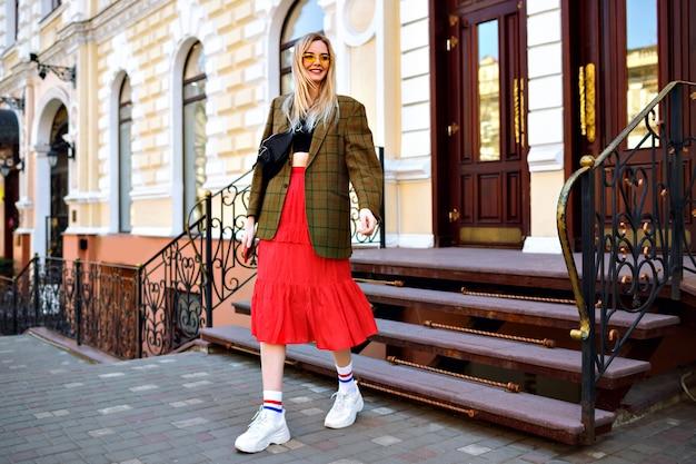 Vrij modieuze prachtige blonde vrouw met plezier op straat na het winkelen, stijlvolle moderne hipster outfit, goede tijd in het centrum van europa.