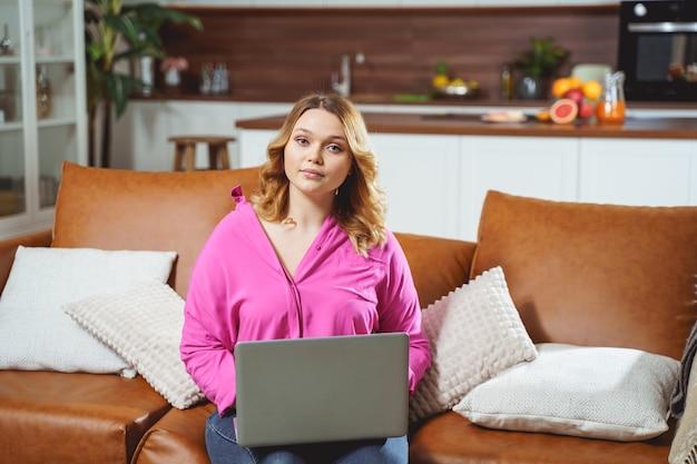 Vrij mollig meisje dat haar laptop op knieën houdt terwijl ze op afstand werkt working
