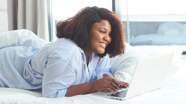 Vrij mollige afro-amerikaanse vrouw begroet haar vriendin online terwijl ze in bed ligt met een laptop