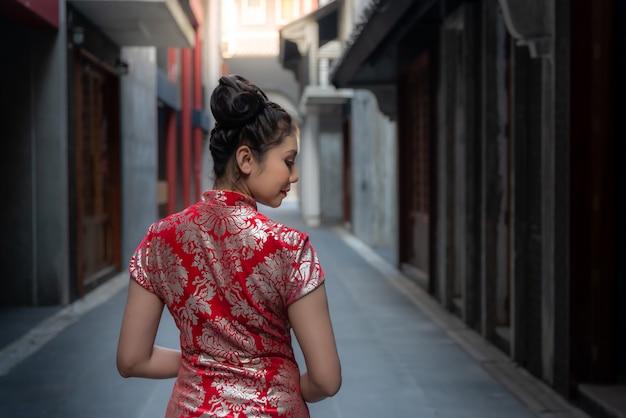 Vrij mooi chinees meisje die een rode cheongsam-kleding dragen die zich op de weg in de stad van china bevinden