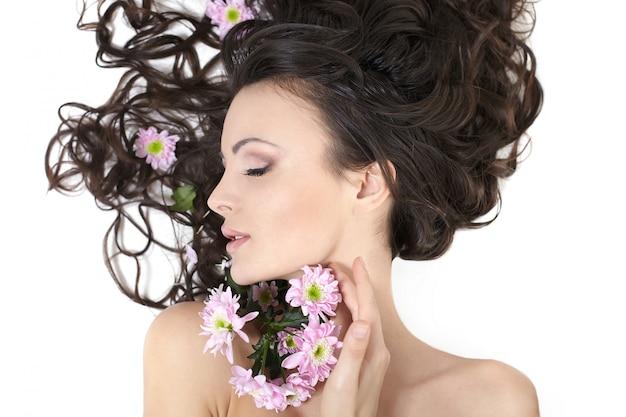 Vrij mooi meisje dat met heldere bloemen in haar haar heldere make-up ligt die op wit wordt geïsoleerd