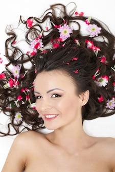 Vrij mooi meisje dat met heldere rode bloemen in haar haar heldere make-up ligt die op wit wordt geïsoleerd