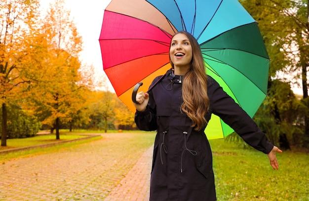 Vrij mooi meisje onder de paraplu van de regenboogregen in het park