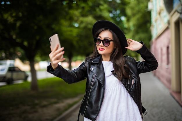 Vrij mooie glimlachende aziatische vrouw die selfie in stadsstraat nemen