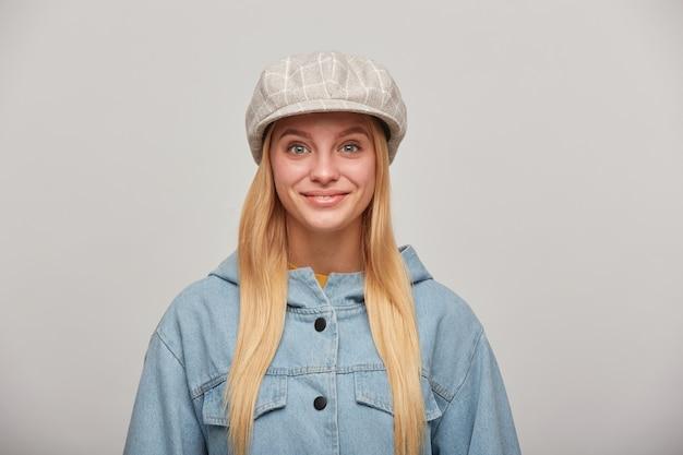Vrij mooie jonge blonde vrouw met lang haar naar beneden, blij kijkend, glimlachend, gekleed in een oversized spijkerjasje en een beige geruite hoed