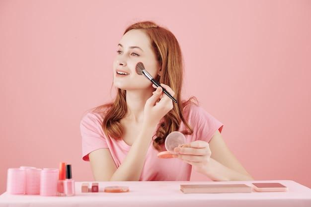Vrij mooie jonge glimlachende vrouw die roze blos op haar wangen aanbrengt wanneer ze 's ochtends make-up doet