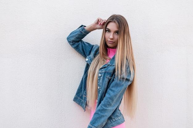 Vrij mooie jonge vrouw in een blauwe modieuze denim jasje met luxe blond lang haar vormt in de stad in de buurt van een vintage gebouw. mooi meisje ontspant buiten op een zomerdag. retro stijl.