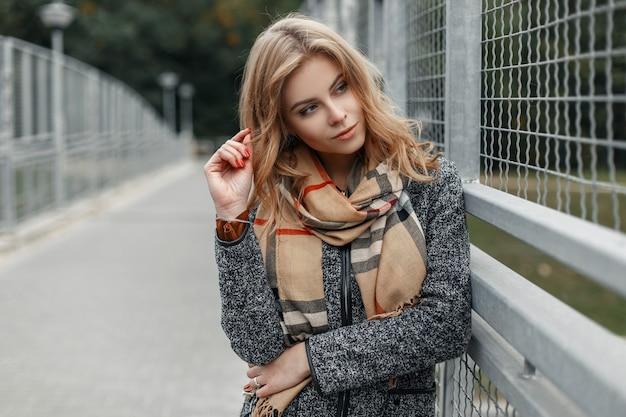 Vrij mooie jonge vrouw in een modieuze grijze jas met een beige vintage sjaal loopt buiten in de buurt van een grijze metalen hek