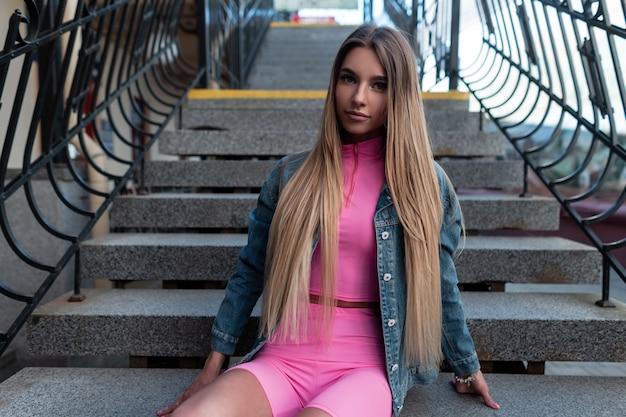 Vrij mooie jonge vrouw met blond lang haar in een vintage jeansjasje in een roze top in een stijlvol roze t-shirt rust op een vintage trap buiten in de straat. aantrekkelijk meisjesmodel ontspant.