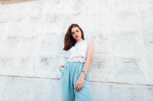 Vrij mooie jonge vrouw model in vintage kant witte blouse in trendy blues broek poseren in de stad in de buurt van de witte muur. aantrekkelijk elegant donkerbruin meisje buitenshuis. stijlvolle zomerkleding voor dames.