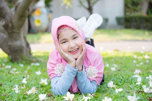 Vrij moslimmeisje die op gras onder een boom en glimlachen liggen.