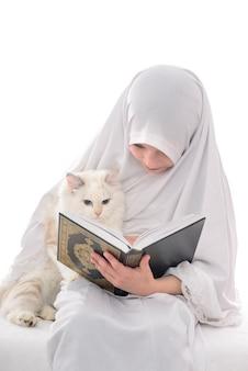 Vrij moslimmeisje en kat die heilige boek van koran lezen