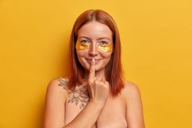 Vrij naakt meisje met sproeten houdt wijsvinger op de lippen, brengt gouden kussentjes aan onder de ogen, vermindert rimpels en donkere kringen, heeft tatoeage op lichaam