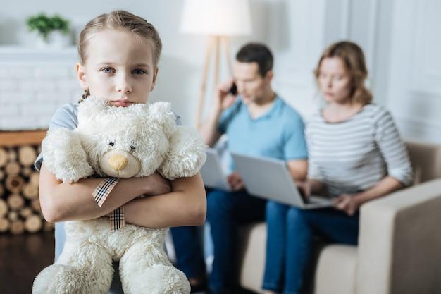 Vrij ongelukkig meisje dat haar teddybeer knuffelt en zich alleen voelt terwijl haar ouders aan hun laptops werken