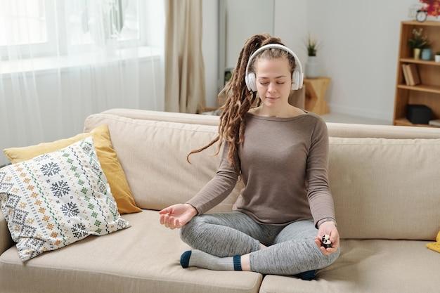 Vrij ontspannen meisje met antistress ballen zittend in de pose van lotus op de bank terwijl mediteren thuis kalmeren