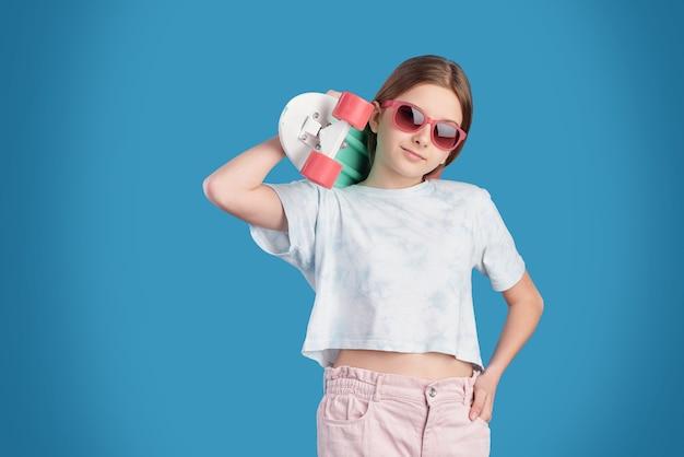 Vrij ontspannen tiener in zonnebril, wit t-shirt en spijkerbroek met skateboard op schouder terwijl hij voor camera staat