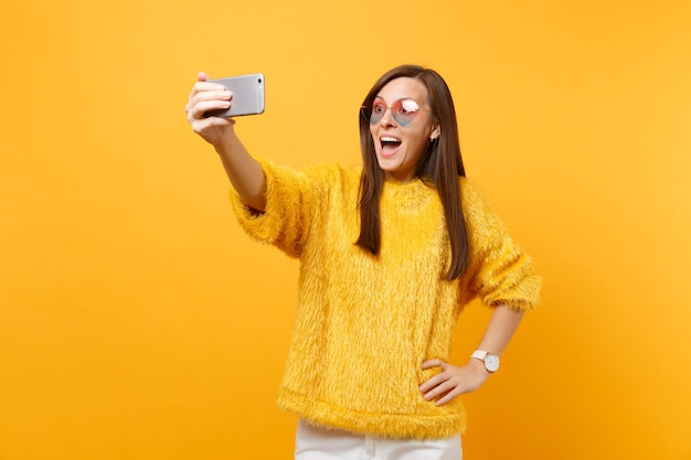 Vrij opgewonden jonge vrouw in bont trui en hart bril doen selfie schot op mobiele telefoon geïsoleerd op heldere gele achtergrond. mensen oprechte emoties, lifestyle concept. reclame gebied.