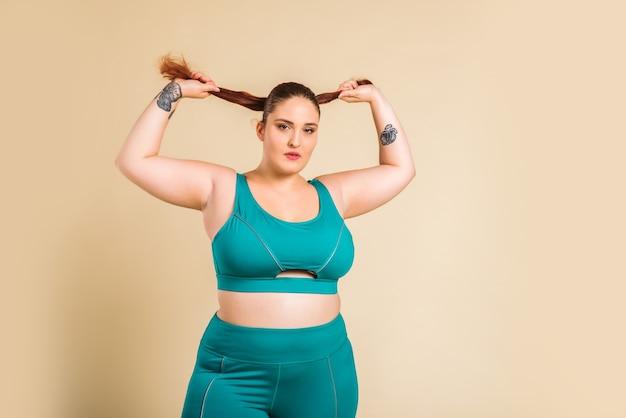 Vrij oversized vrouw, gekleed in sportkleding poseren in de studio