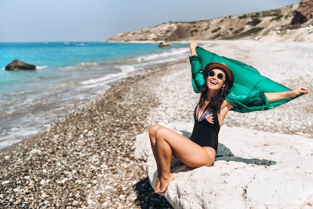 Vrij pan het aziatische reismeisje ontspannen op het strand bij het overzees in groene pareo.