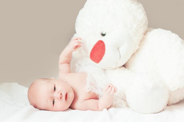 Vrij pasgeboren babymeisje met een groot zacht stuk speelgoed dat op de deken ligt. foto met kopieerruimte