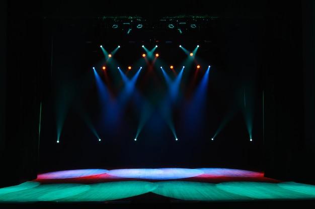 Vrij podium met verlichting, achtergrond van leeg podium, spotlight, neonlicht, rook.