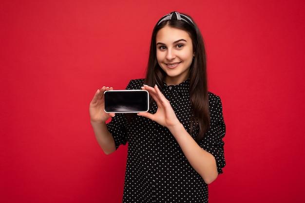 Vrij positief lachend donkerbruin meisje dat geïsoleerd staat over een rode muur en casual stijlvolle zwarte kleding draagt