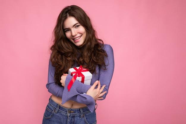 Vrij positief lachende brunette krullend jonge vrouw geïsoleerd op roze oppervlak muur dragen paarse blouse met witte geschenkdoos met rood lint en camera kijken