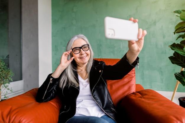 Vrij positieve vrolijke 60-jarige vrouw met recht grijs haar, die zich voordeed op haar smartphone voor selfie foto, zittend in rode fauteuil voor groene muur in studio