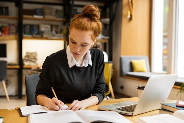Vrij rode haired tiener die laptop computer met behulp van