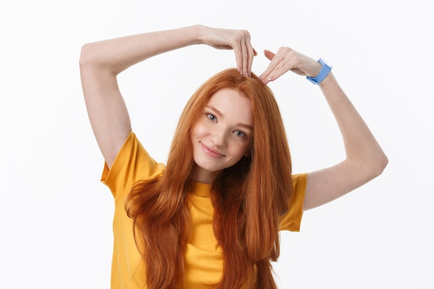 Vrij romantische jonge roodharigevrouw die een hartgebaar met een gelukkige tedere glimlach maakt