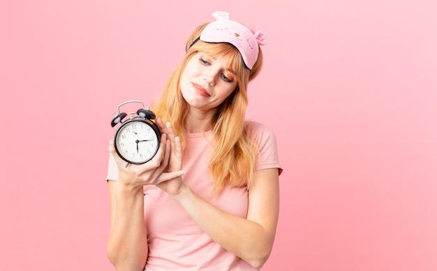 Vrij roodharige vrouw die pyjama's draagt en een wekker houdt. wakker worden concept
