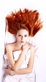 Vrij roodharige vrouw in witte nachtjapon die in het bed ligt. foto in vogue-stijl.