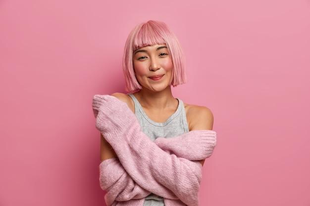 Vrij roze harige jonge vrouw knuffelt zichzelf, draagt een warme trui, wacht op een speciaal moment, voelt troost, drukt oprechte emoties uit, geniet van geweldige zachte kleding,