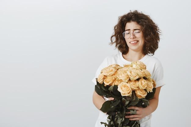Vrij sceptisch meisje krimpt ineen als ze naar bloemen kijkt, niet van rozen houdt, niet onder de indruk is