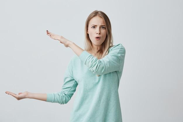Vrij schattig blonde vrouw die vrijetijdskleding draagt die iets groots met handen laat zien, haar wenkbrauwen fronst, lippen pruilt.