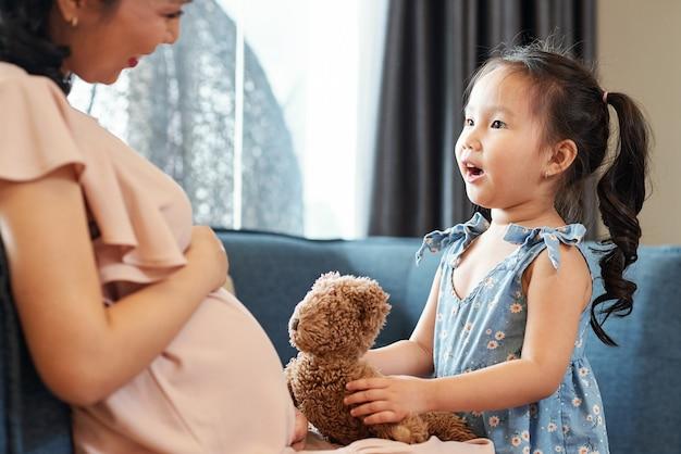Vrij schattig klein meisje met teddybeer in gesprek met haar zwangere moeder over toekomstige broer of zus