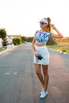 Vrij schattig meisje met retro camera poseren tijdens road trip op zonnige zomerdag.