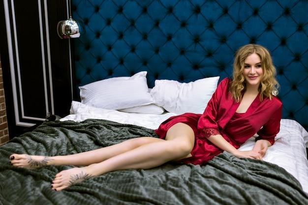Vrij sensueel blond model liggend op het bed, geniet van haar ochtend in een luxehotel, gekleed in bordeauxrood zijden nachthemd en gewaad, blinde haren en schoonheidsgezicht, boudoir-stijl.