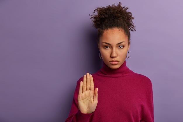 Vrij serieuze vrouw trekt handpalm, toont geen afwijzingsgebaar, weigert of zegt wacht even, gekleed in casual poloneck, niet in iets geïnteresseerd, probeert iemand te kalmeren. stop hier
