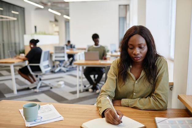 Vrij serieuze zakendame zit aan een bureau met een kopje koffie en gedrukte rapporten en neemt...